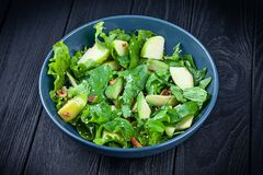 View from above on fresh, homemade vegan bowl. vegetarian salad spinach and avocado in blue bowl on dark wooden background. Copy royalty free stock image