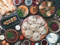 Georgian cuisine on wooden table, top view. View from above of georgian cuisine on brown wooden table. Traditional georgian cuisine and food - khinkali, kharcho stock images