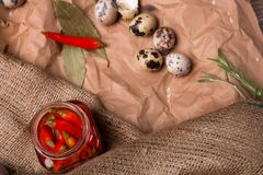 Quail eggs, hot red peppers in a jar, and green rosemary on a crumpled paper and brown fabric. Organic ingredients. royalty free stock images