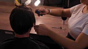 View from above. The hairdresser woman trims the temporal part of the young man and pulling her hair cuts off the ends