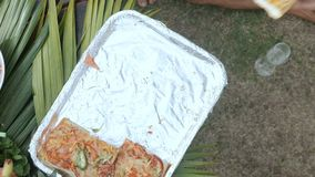 View from above on hands pick up pieces of pizza from picnic party table stock video footage