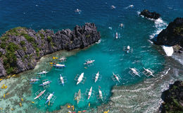 A view from above on a lagoon in which boats brought tourists for a rest. Aerial view of the turquoise water between the black st royalty free stock photography