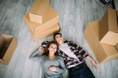 View from above, looking at the camera a young couple lying on the floor of their new home royalty free stock photos