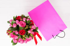 View from above of a lovely bouquet of pink and red roses and re. D ribbon in a circular black box near pink gift bag. Valentines and anniversary concept Royalty Free Stock Images