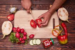 Top view of a man cutting a fresh red tomato. Vegatbles around cutting desk on a table background. stock images
