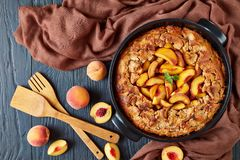 View from above of an old fashioned Peach Cobbler. Served with fresh ripe peaches, together with kitchen wooden tools: a slotted Turner-Spatula and a flat stock photo