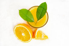 View from above orange juice with ice cubes,leaves on ice on white Royalty Free Stock Photography