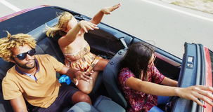 View from above of people dancing to music while driving in convertible, graded. View from above of young people dancing to music while driving in convertible stock video footage