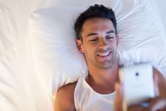 View from above of portrait of handsome smiling young man using. A mobile phone and messaging in the white bed Royalty Free Stock Photo