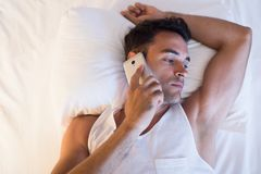 View from above of portrait of handsome young man using a mobile. Phone in the white bed Stock Photography