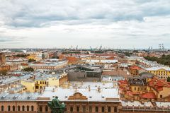 View from above on the roofs of St. Petersburg streets and the port on a cloudy day. View from above on the red yellow roofs of St. Petersburg streets and the royalty free stock image