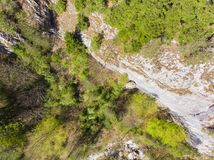 View from above of a rocky wall. With some pines in the spring stock photography