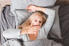 Woman stretching in bed after wake up stock images