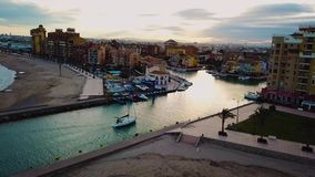 View from above on small yacht during sunset on Mediterranean sea coast near Valencia. Windy and colorful evening in Spain. Filmed on beach without people near stock video
