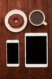 View from above of smartphone, tablet pc, donut and coffee Stock Images