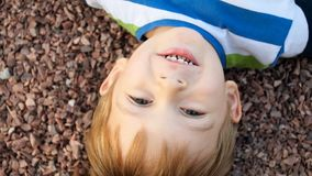 View from the above on cute smiling toddler boy lying on ground and looking at camera. View from the above on smiling toddler boy lying on ground and looking at stock video