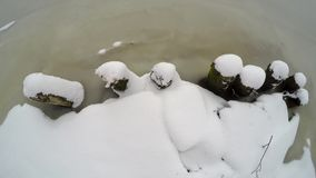 View from above on a snow-covered shore of the river stock video