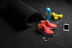 Top view of bright yellow dumbbells, a mat, bottle of water, sports shoes and phone on a black floor background. royalty free stock image