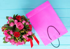 View from above on stylish bouquet of pink and red roses and red. Ribbon in a circular black box near pink gift bag. Valentines and anniversary concept Stock Images
