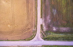 View from above to field of wheat and empty gravel rural road in Lithuania. Mazeikiai. Royalty Free Stock Image