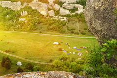 View from above to the valley among the mountains.  Tents on the green grass. View from the top of the valley among the mountains. Tents on the green grass far Stock Images