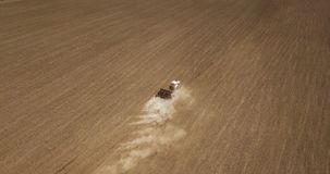 View from above of Tractor works in a field and plowing. Aerial view of a tractor plowing a farm field in preparation for spring planting. Industrial background Stock Images