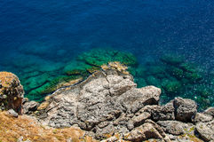 View from above on transparent blue sea water and rocks Royalty Free Stock Images