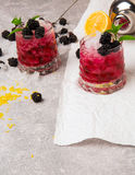 A view from above on two big glasses of cold beverages with berries and ice on gray and white background. Healthful and Royalty Free Stock Photography