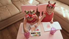 View from above. Two charming little sisters twins draw watercolor on paper, sitting at a table in their room at home. stock video footage