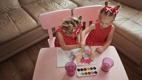 View from above. Two charming little sisters twins draw watercolor on paper, sitting at a table in their room at home. stock footage