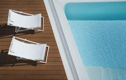 View from above of two white canvas chaise lounge chairs positioned on a brown outdoors wooden deck by a turquoise infinity pool royalty free stock images