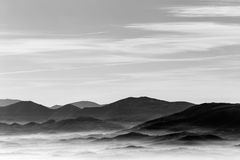 A view from above of a valley filled by a sea of fog, with vario Royalty Free Stock Image