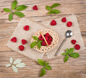 View from above of wicker basket with raspberries. Top view of small basket with fresh raspberries with leaves on wooden background Royalty Free Stock Photo