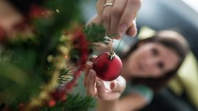 View from above of a woman placing red holiday bauble on Christmas tree stock photos