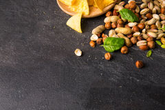A view from above on yellow nachos, roasted peanuts, peeled hazelnuts and cracked pistachios on a black background. Copy Royalty Free Stock Image