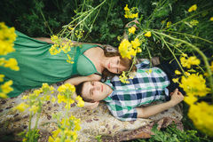 View from above of young couple of boyfriend and girlfriend lying on grass among yellow flowers in meadow. Woman in green dress an Stock Images
