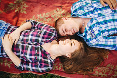 View from above of young couple of boyfriend and girlfriend lying on ground looking at camera.. Woman and man wearing in checked s Royalty Free Stock Photos