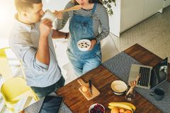 View from above. Young couple in kitchen cooking breakfast. Man is standing near table and drinking tea Royalty Free Stock Photography