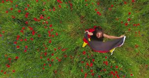 View from above of young girl dancing in a poppy field holding flag of Germany in hands outdoors. Connection with nature. Pretty girl dancing in a poppy field stock footage