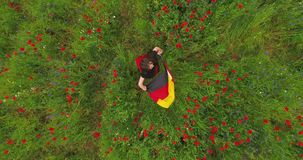 View from above of young girl dancing in a poppy field holding flag of Germany in hands outdoors. Connection with nature. Pretty girl dancing in a poppy field stock video