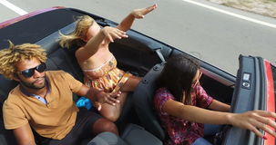 View from above of young people dancing to music while driving in convertible stock footage