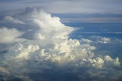 View of abstract dense soft fluffy white cloud with shades of blue sky and earth background from above flying plane window stock images
