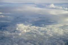 View of abstract soft white cloud shape with shades of blue sky background from above flying plane window Stock Images