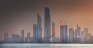 View of Abu Dhabi Skyline at misty sunrise, UAE. View of Abu Dhabi Skyline at misty sunset, United Arab Emirates stock photography