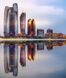 View of Abu Dhabi Skyline at sunrise, UAE. View of Abu Dhabi Skyline at sunrise with cloudy sky and reflection of buildings on water, United Arab Emirates Royalty Free Stock Photos