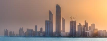 View of Abu Dhabi Skyline at sunrise, UAE. Sunrise scenery view of Abu Dhabi skyline with reflection of sun on buildings, United Arab Emirates Royalty Free Stock Photo