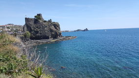 View of Acitrezza`s Castle. And the sea in front of it, the blue color of the sea and the rocky walls of the castle lying on the sea Royalty Free Stock Photo