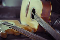 Electric Vs Acoustic. View of acoustic and electric guitars lying on leather sofa Royalty Free Stock Photos