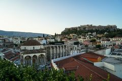 View of the Acropolis mountain, from Monastiraki Square through old town buildings roof, green leaves foreground Stock Photos