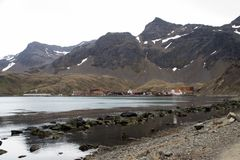 View across bay of old whaling station site surrounded by mountains stock image